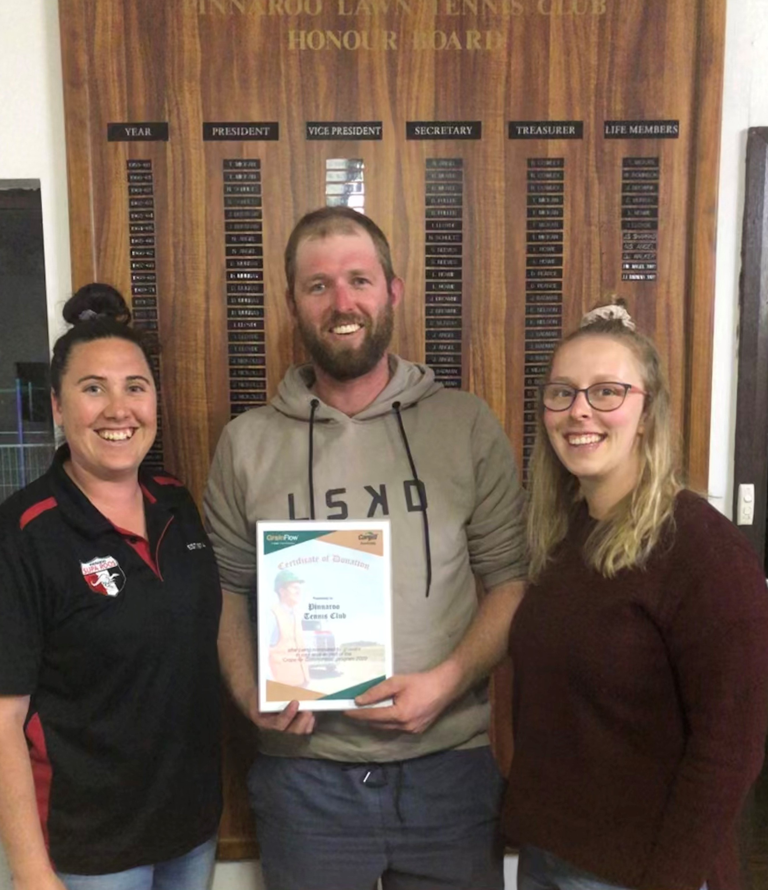 Joel (President), Steph (treasurer) and Georgia (committee member) Heinicke, in front of the life members board at the Pinnaroo Tennis Club
